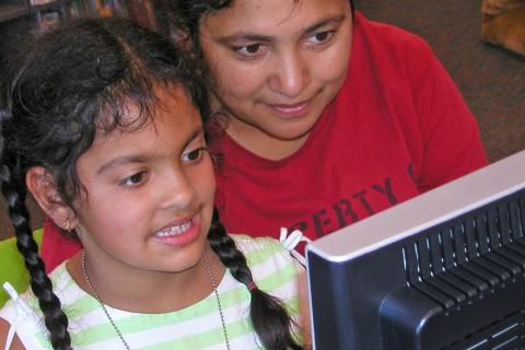 Picture of a small girl looking at a computer in a library - CREDIT: San José Public Library